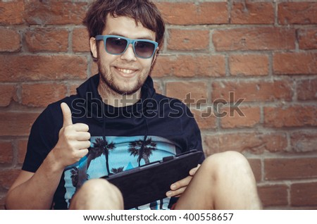 Bearded  young stylish hipster man using tablet sitting next to a brick wall