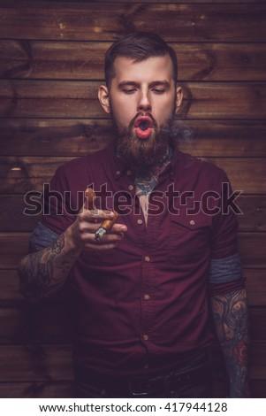 Beardedm guy with tattooed hands smoking cigar. - stock photo