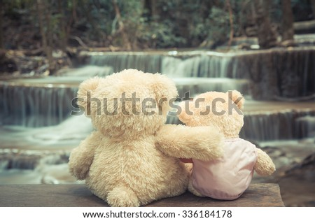 Bears in love hugs in vintage waterfall background - stock photo