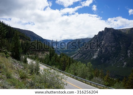 Beartooth highway through Wyoming, Montana. The most scenic drive in the US on the way to Yellowstone National Park surrounded by lush greenery and mountain peaks - stock photo
