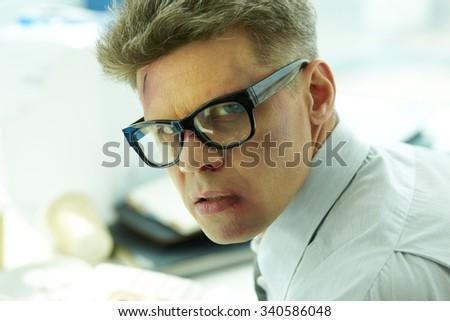 Beaten businessman in eyeglasses looking at camera - stock photo