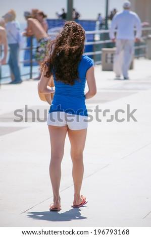 Beatiful female model wearing white shorts and blue shirt on beach pier walking. - stock photo