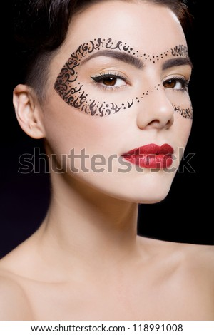 Beatiful girl with make up and mask on the black background