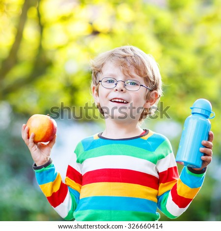 Beatiful little kid boy with  apple and drink bottle on his first day to elementary school or nursery. Outdoors.  Back to school, kids, lifestyle concept - stock photo