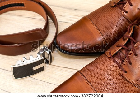 Beatiful pair of luxurious men's leather shoes accompanied by a leather belt.