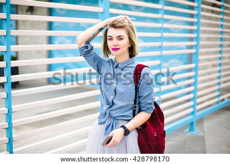 Beatiful tattooed girl with pink lips holding her hair with one hand and smartphone with another hand, wearing blue denim shirt,skirt and marsala backpack with blue and white stripes on the background - stock photo