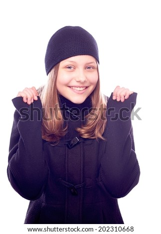 Beatiful teen girl dressed in coat and hat posing and smiling