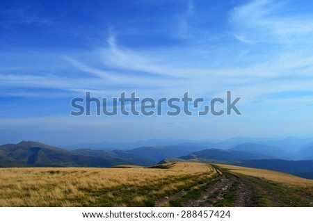 beatiful view on the mountain range on the bakground and road on the front and blue sky on the top with the space for text
