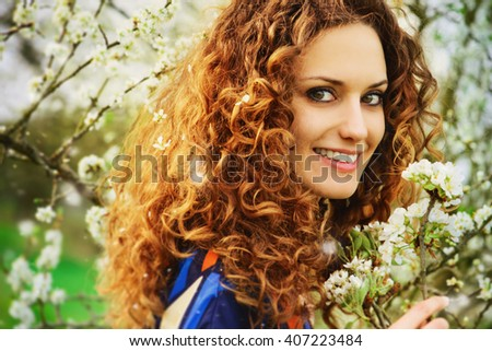 Beatutiful smiling young woman and the cherry blossom trees