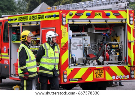 Beaulieu, Hampshire, UK - May 29 2017: Two British firemen or firefighters standing at the rear of a modern fire engine or tender