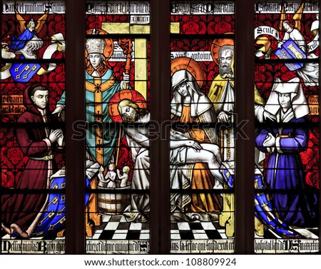 BEAUNE, FRANCE - APRIL 30: The stained glass window of Piety, with Chancelor Rolin and his wife Guigone de Salins, Saint Nicholas, and Saint Anthony the Great at Hotel Dieu in Beaune, France on April 30, 2012 - stock photo