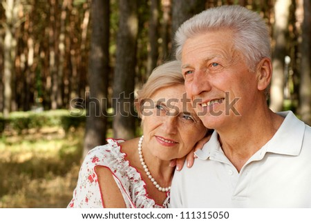 Beauteous elderly couple went for a walk in the forest