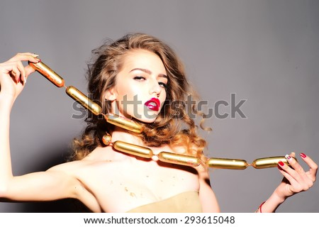 Beauteous young girl with curly hair holding wrapped gold sausages on neck looking forward standing on grey background copy space, horizontal picture - stock photo