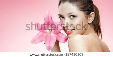 Beauteous young woman with flower / studio photo of brown-eyed brunette girl holding pink lily flower and smiling - isolated on pink background