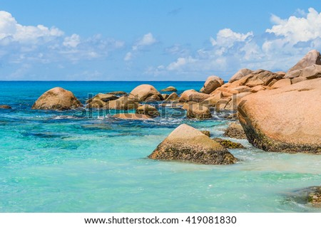 Beautful tropical landscape of the shallow water rocky ocean beach of the Seychelles Island - stock photo