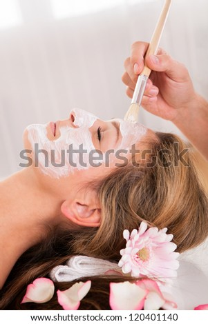 Beautician applying a face mask to a beautiful blonde woman lying relaxing in the salon with her eyes closed