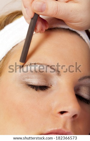 Beautician applying eyebrow pencil for darkening the Eyebrows of a young Woman