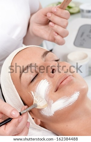 Beautician applying facial cream on womans face, woman laying eyes closed with headband. - stock photo