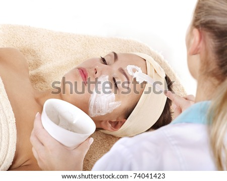 Beautician applying  facial mask by young woman. - stock photo