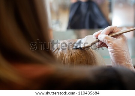 Beautician applying hair color to woman at parlor - stock photo