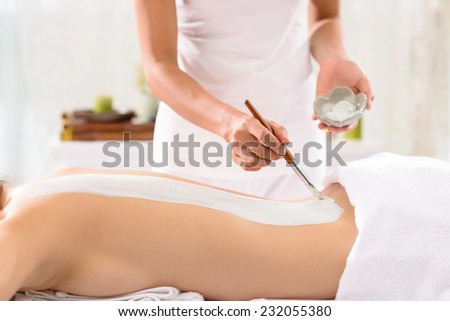 Beautician applying treatment to the back of the client - stock photo