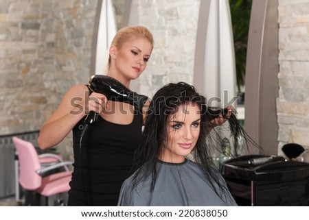 Beautician blow drying woman's hair after giving new haircut at parlor. blond girl drying dark-haired girl hair - stock photo