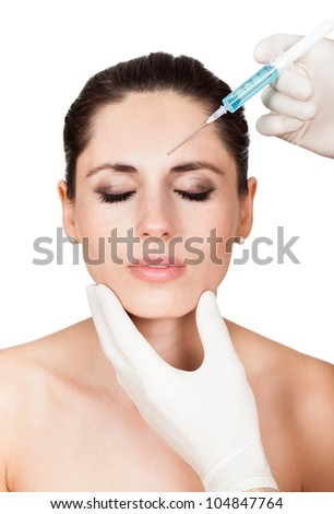 Beautician doing injection to the beautiful female face - stock photo
