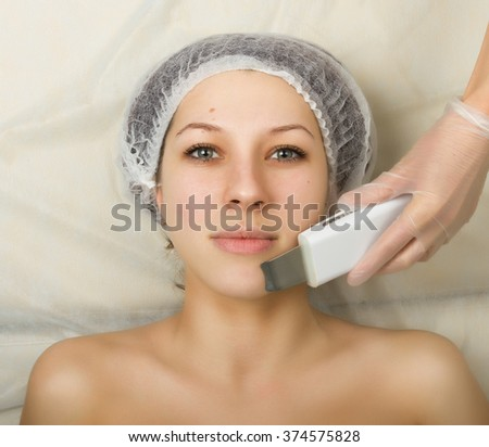 Beautician examining the face of a young female client at spa salon. ultrasonic cleaning person. Professional consultation.  - stock photo
