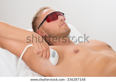 Beautician Giving Laser Epilation Treatment On Man's Armpit - stock photo