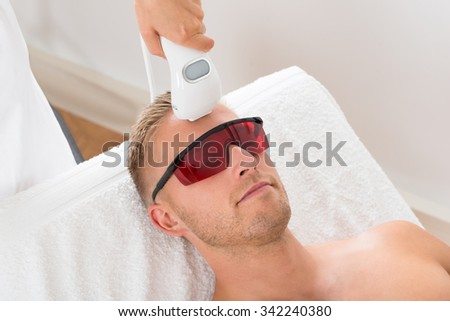 Beautician Giving Laser Epilation Treatment On Young Man - stock photo
