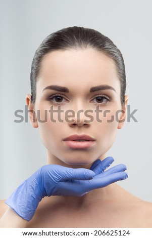 Beautician in blue rubber gloves touching face of young beautiful woman. Plastic surgery. Close up portrait isolated on grey background - stock photo