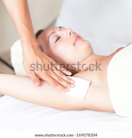 Beautician removing body hair - stock photo