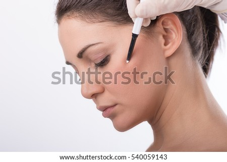 Beautician touch and draw correction lines on woman face. Before plastic surgery operation. Isolated on white.