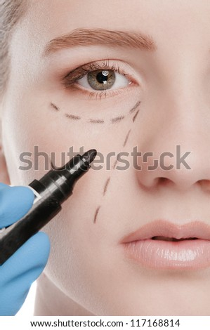 Beautician touch and draw correction lines on woman face. Before plastic surgery operetion. Isolated on white - stock photo