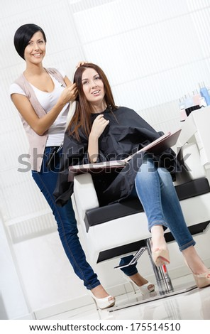 Beautician tries lock of dyed blond hair on the client sitting on the chair in the hairdress salon - stock photo