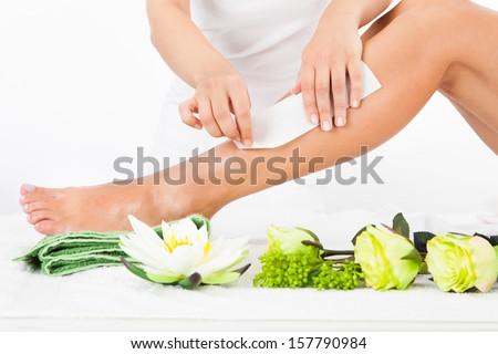 Beautician Waxing A Woman's Leg In Spa - stock photo