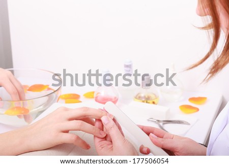 Beautician with file filing nails female client. Woman spa beauty salon - stock photo