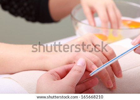 Beautician with file filing nails female client. Woman spa beauty salon, manicure - stock photo