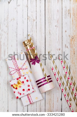 Beautified mini champagne and handmade gifts on a wooden background. View from above - stock photo