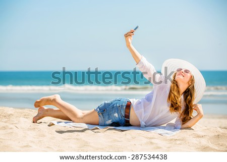 Beautifil young caucasian woman lying on the beach in white hat and taking selfie picture with mobile phone sunny day on summer vacation