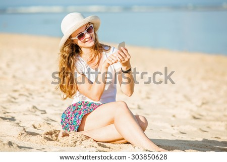 Beautifil young caucasian woman on the beach in white hat  with mobile phone. Sunny day on summer vacation - stock photo