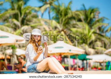 Beautifil young caucasian woman sitting on the beach in white hat with mobile phone in her hand at sunny day enjoing summer vacation