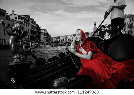 Beautifiul woman in red cloak riding on gandola - stock photo