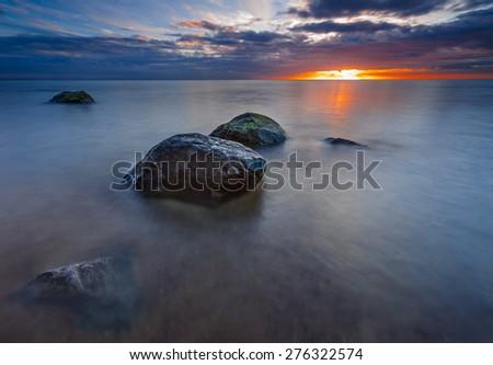 Beautifu rocky sea shore at sunrise or sunset. Long exposure landscape. Baltic sea near Gdynia in Poland. - stock photo