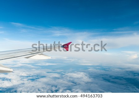 beautifu wing of plane on cloud and blue sky taken on plane at sunny day, subject is blurred