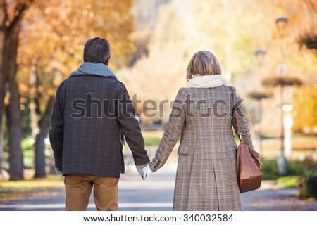 Beautiful  active seniors on a walk in a town park