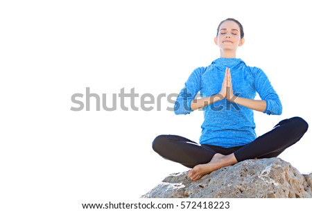 Beautiful active woman sitting in a yoga position on a rock against a sunny sky, practicing yoga with her hands together and eyes closed, space. Fitness, sport, health, wellness recreation lifestyle.