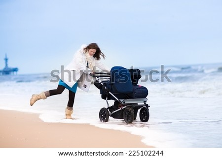 Beautiful active young mother walking on a beach pushing an all terrain double stroller with two children, baby and toddler, on a cold winter day in Holland - stock photo