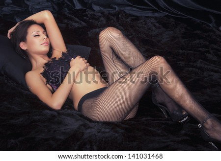 Beautiful actress model in fishnet stockings lying on bed - stock photo