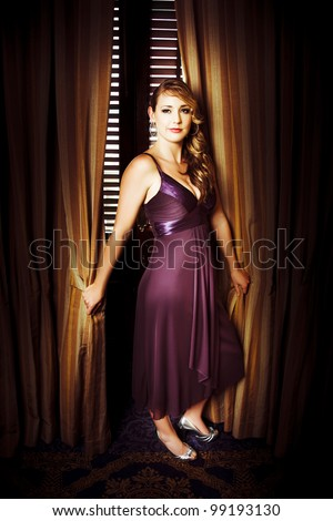 Beautiful actress wearing a purple evening dress with long curly blonde hair posing in front of ornate gold curtains for her portrait at the premiere of her latest film - stock photo